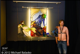 princeHerman standing in front of large stained glass piece